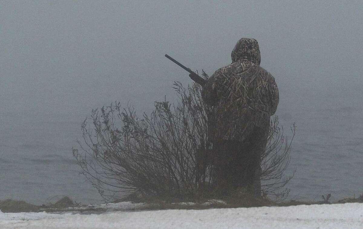 A goose hunter eyes a foggy Norwalk Harbor as he waits for his quarry at Veteran's Memorial Park on Jan. 12, 2018 in Norwalk.