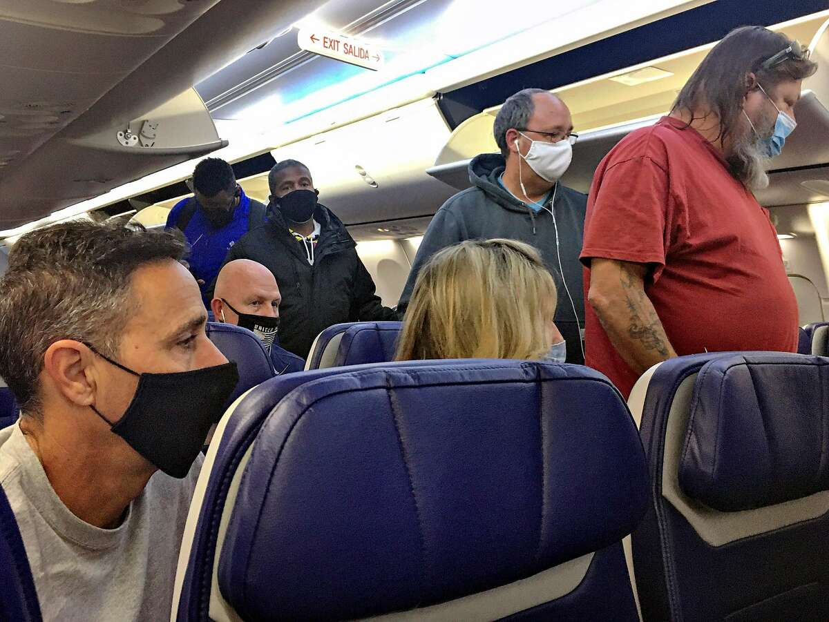 Masked passengers board a flight to Oakland on Nov. 15. Virus cases are increasing alarmingly, and holiday gatherings are likely to take another toll.