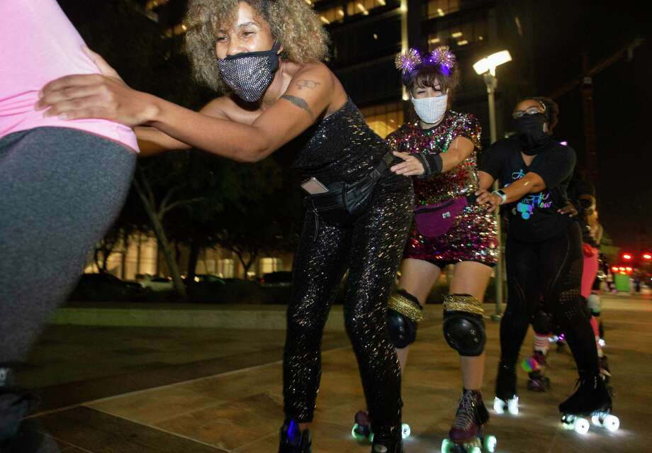 The Space City Roller members skate like a train while having fun with a Friday night skate Friday, Nov. 20, 2020, at Discovery Green in downtown Houston. The Space City Roller is a Houston-based girl group of roller skaters. Photo: Yi-Chin Lee, Houston Chronicle / Staff Photographer / © 2020 Houston Chronicle