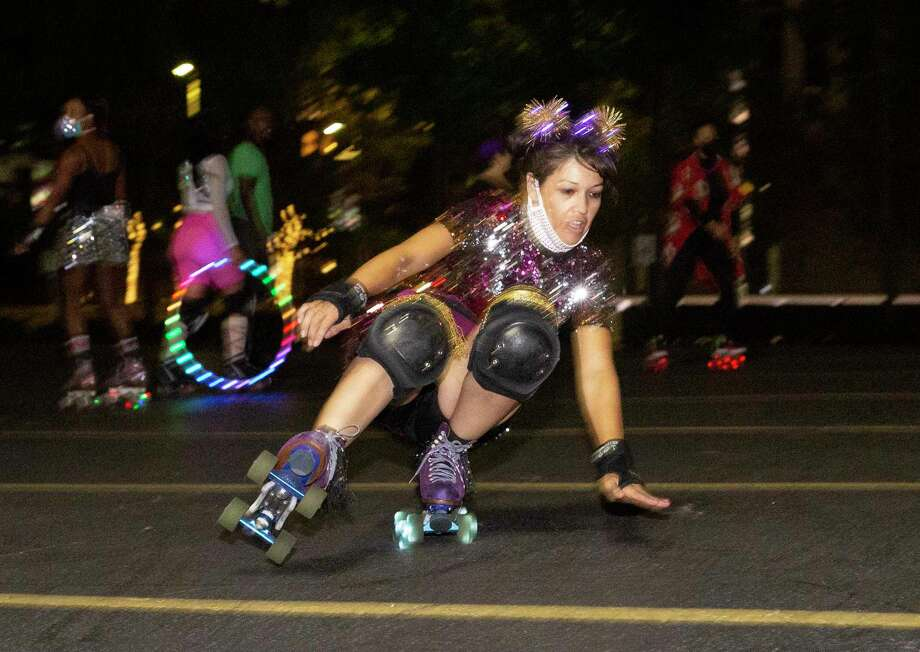 Sherry Carabes skates in freestyle while the Space City Roller members are having fun with a Friday night skate Friday, Nov. 20, 2020, at a parking lot in downtown Houston. The Space City Roller is a Houston-based girl group of roller skaters. Photo: Yi-Chin Lee, Houston Chronicle / Staff Photographer / © 2020 Houston Chronicle