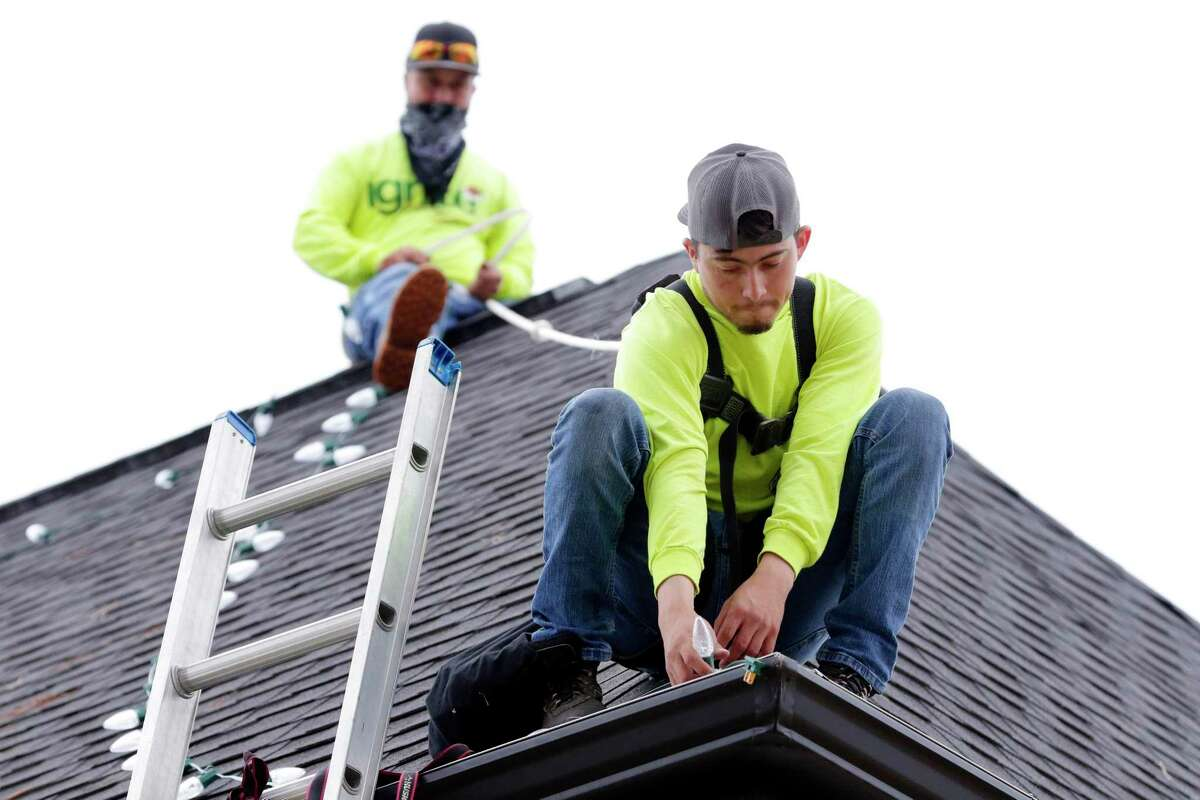 Brothers, from left, Federico Dorrijos and Daniel Dorrijos, with Ignite Christmas Lighting, install strings of white lights on the roof of a home in the Heights area.