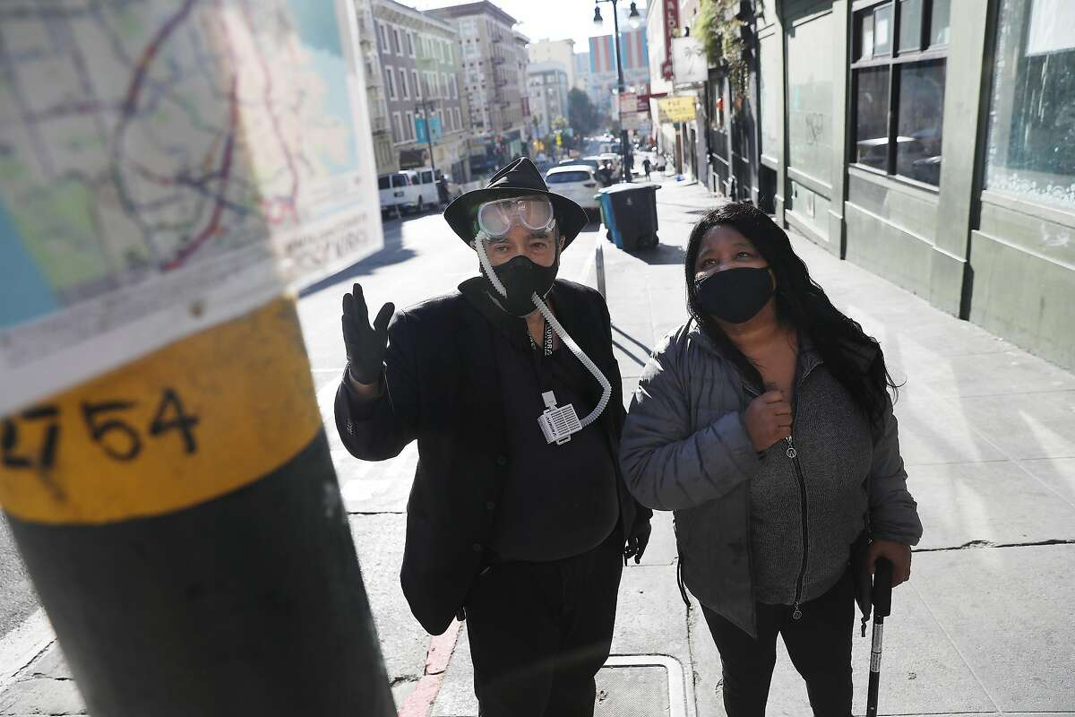 David Elliott Lewis (left), Central City SRO tenant advocate, and Cheryl Shanks of the Tenderloin Neighborhood Development Corporation examine signage at a Muni stop where they used to be able to catch the 27 line.