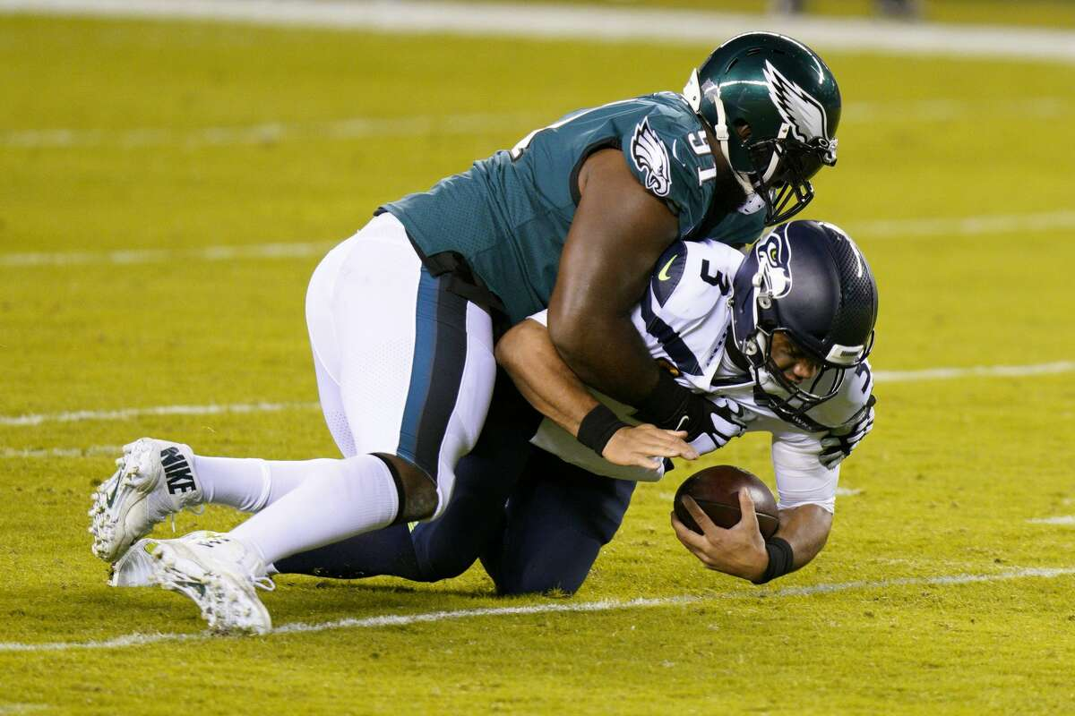 Philadelphia Eagles' Fletcher Cox (91) tackles Seattle Seahawks' Russell Wilson (3) during the first half of an NFL football game, Monday, Nov. 30, 2020, in Philadelphia. (AP Photo/Chris Szagola)