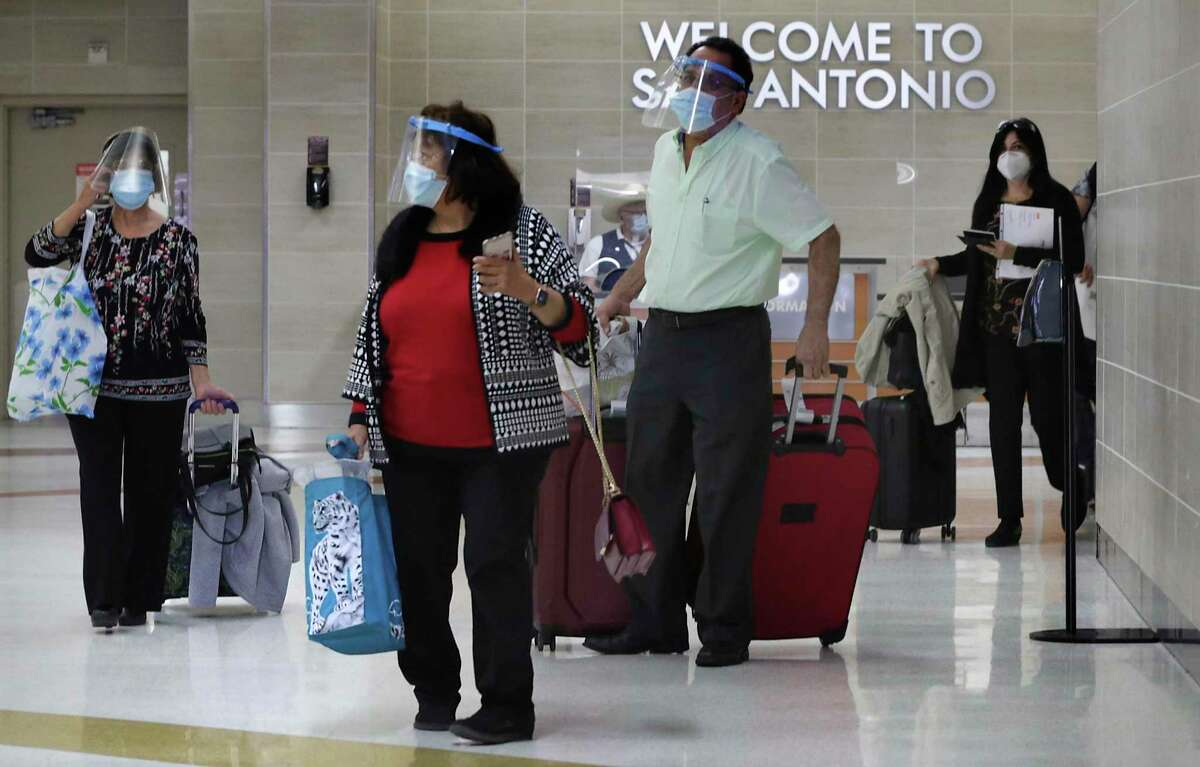 Travelers wearing face masks and face shields arrive at the San Antonio International Airport to visit for the upcoming Thanksgiving celebrations, on Monday, Nov. 23, 2020.