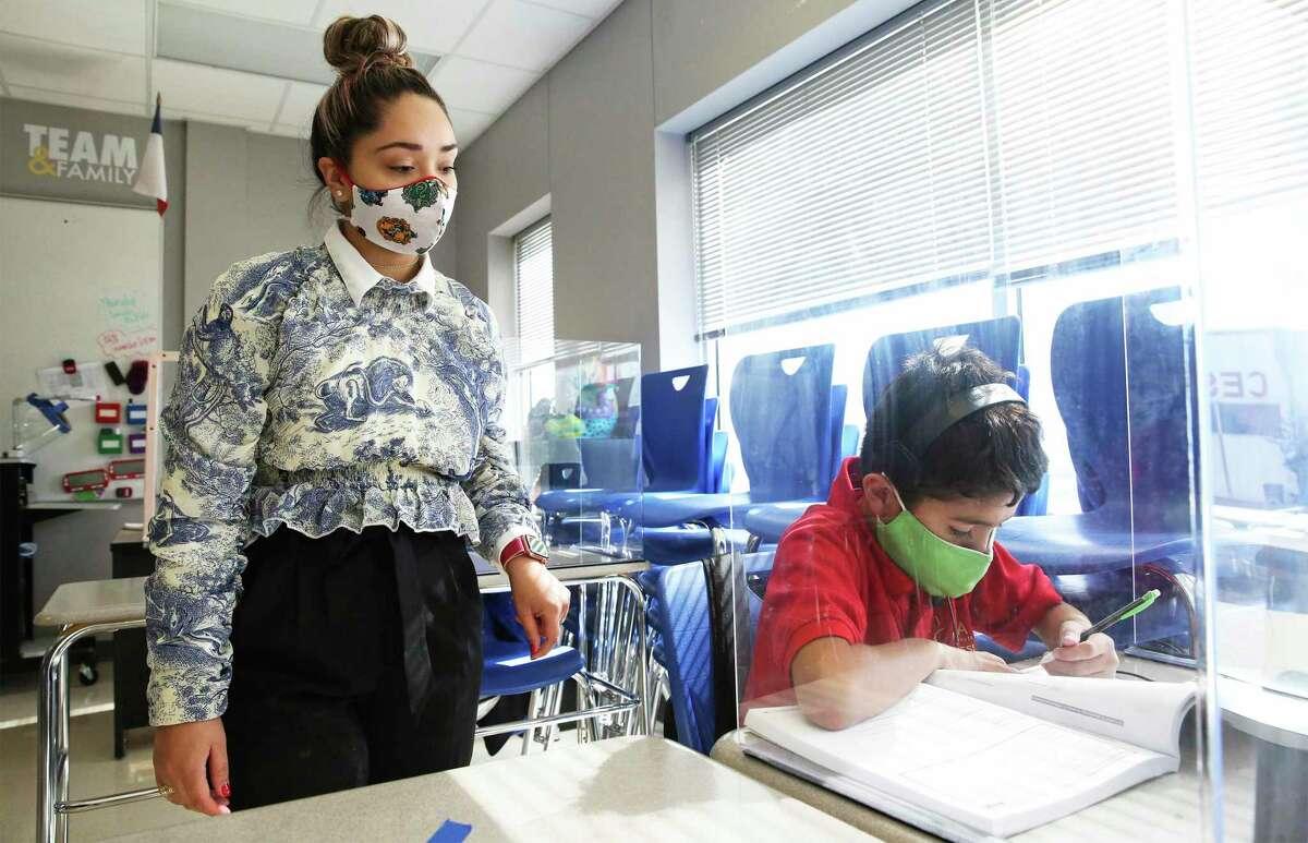Sixth grade teacher Hosanna Diaz watches over a student's work at IDEA Carver College Preparatory on Monday.