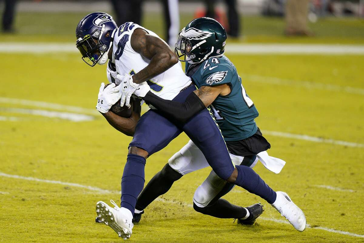 Seattle Seahawks' DK Metcalf, left, is tackled by Philadelphia Eagles' Darius Slay during the first half of an NFL football game, Monday, Nov. 30, 2020, in Philadelphia. (AP Photo/Chris Szagola)