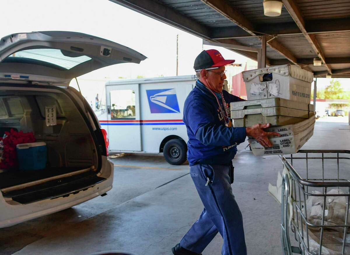 Postal Service letter carrier Marcos Perez removes empty trays from his vehicle upon returning to the Arsenal post office on his last day of work on Monday, Nov. 30, 2020.