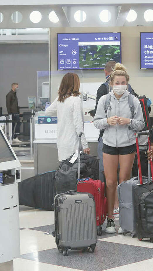 Travelers talk in a terminal at O'Hare International Airport in Chicago during Thanksgiving. Health officials are concerned there could be a surge of COVID-19 cases after people spent time in larger groups for the holiday. Photo: Teresa Crawford | AP