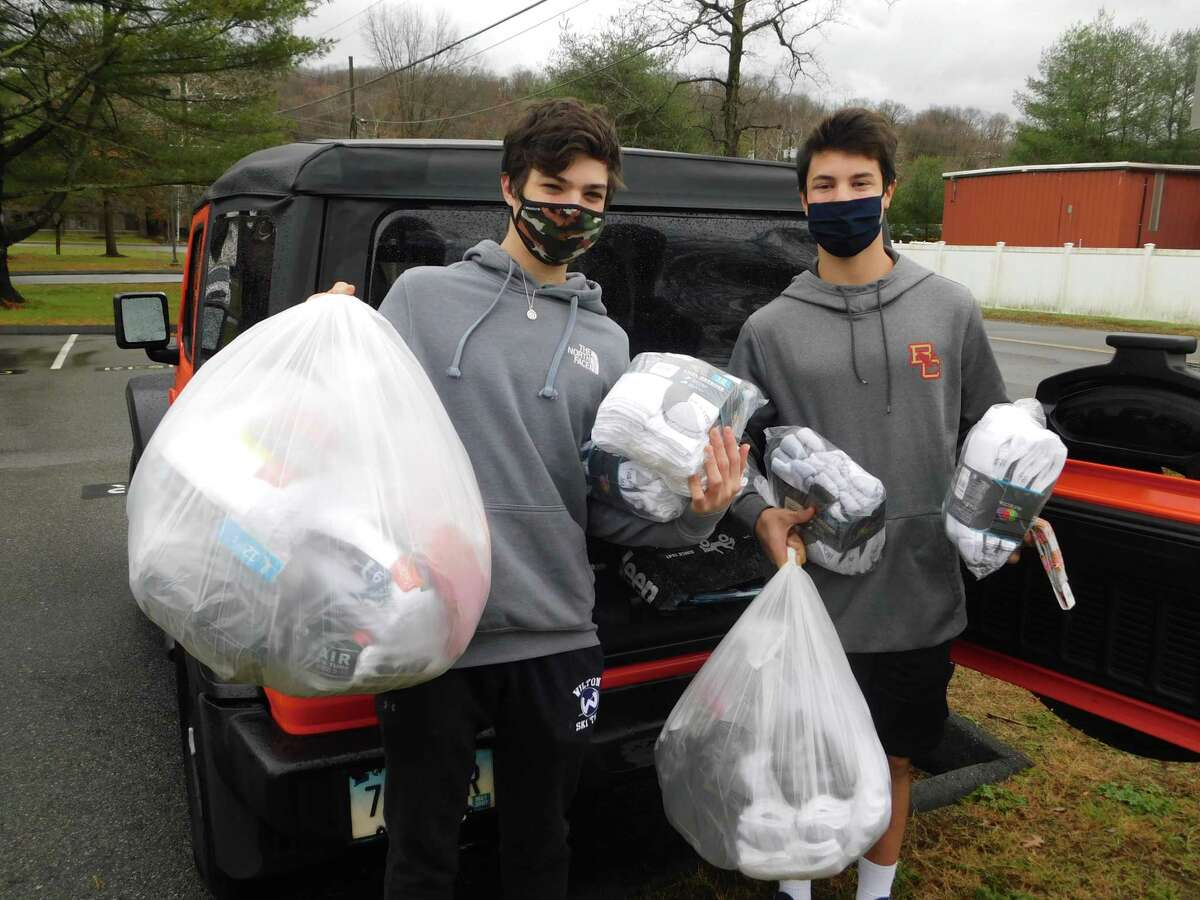 Wilton High School students Elijah Ackerman and Tyler Casey hold bags of socks to be donated to soldiers and veterans. The socks were collected by the Socks for Soldiers club during its Veterans Day drive.