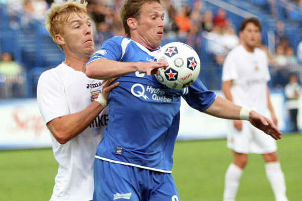 Edwardsville graduate Luke Kreamalmeyer, right, of the Montreal Impact tries to control the ball against the Fort Lauderdale Strikers in NASL action in July 2011 in Montreal.