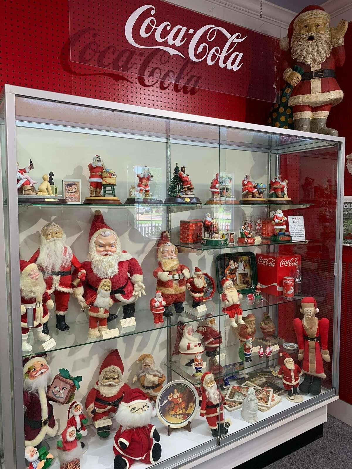 Collection of Santas in a Coca-Cola display case.
