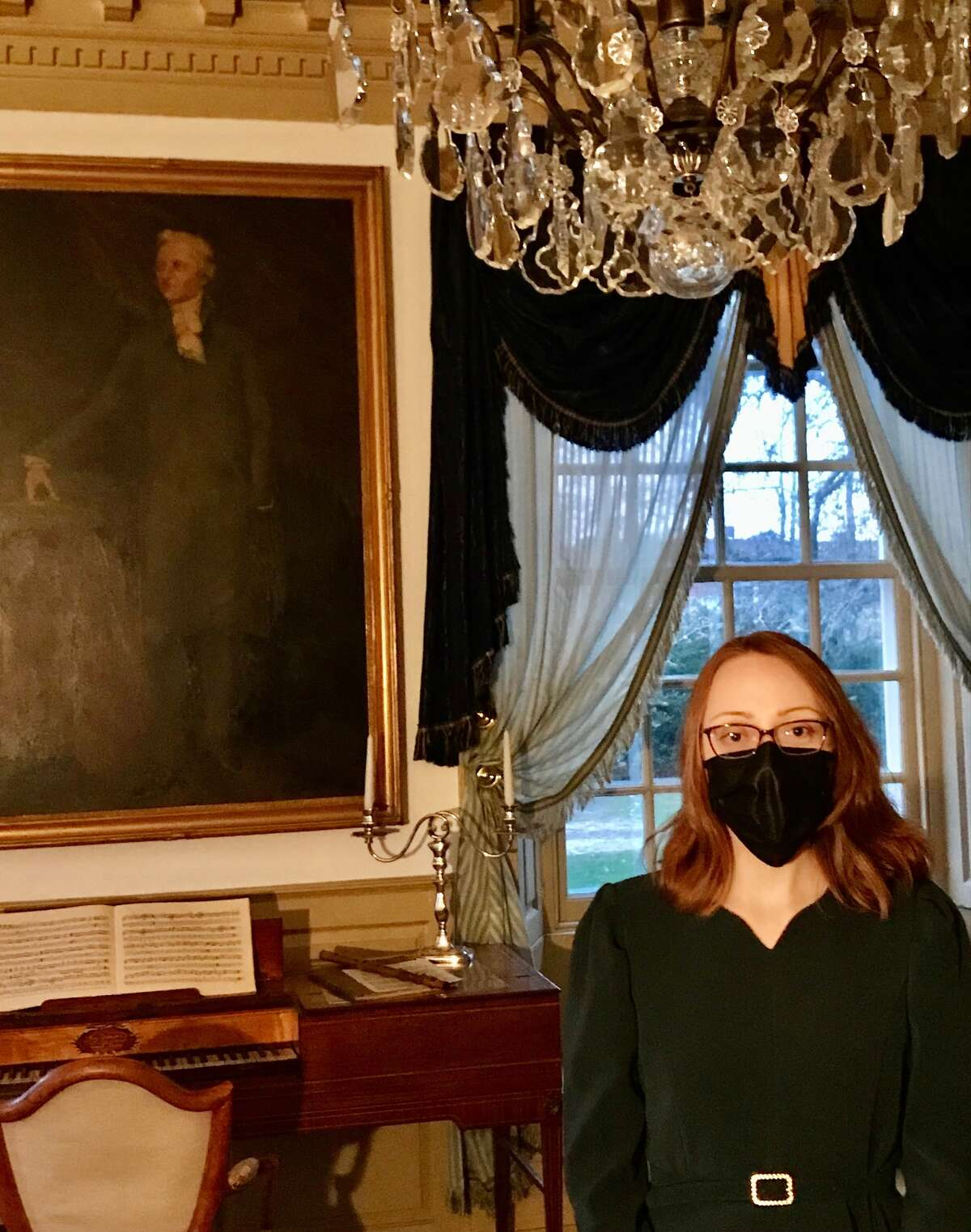 Jessie Serfilippi, who has an MFA in creative writing and primarily writes fiction, stands beneath a portrait of Hamilton in the blue room,  where Hamilton married Schuyler's daughter, Elizabeth, on Dec. 14, 1780.