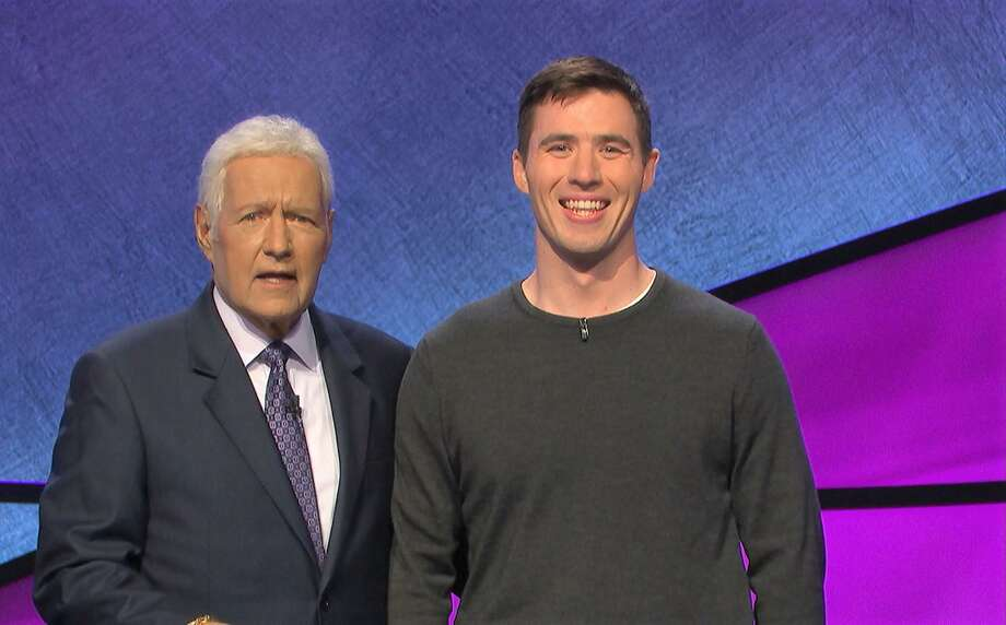 """Many Wesleyans have competed on """"Jeopardy!"""" over the years. J.R. Mannetta '13, right, is pictured on set in January with host Alex Trebek, who died Nov. 8. J.R. Mannetta '13 competed in January. """"When you go on 'Jeopardy!' you don't actually speak with Alex until the episode is recording and they do your interview segment, which is my way of saying beyond that conversation I didn't interact with Alex much. He does do Q&A during commercial breaks, and, despite obviously not being at 100 percent physically, he was still very much with it mentally. He still had a very quick wit and is bitingly funny. """"I watched 'Jeopardy!' religiously from high school to now and I can't fathom what the show will look like without him,"""" Mannetta said. Photo: Contributed Photo / Wesleyan University"""
