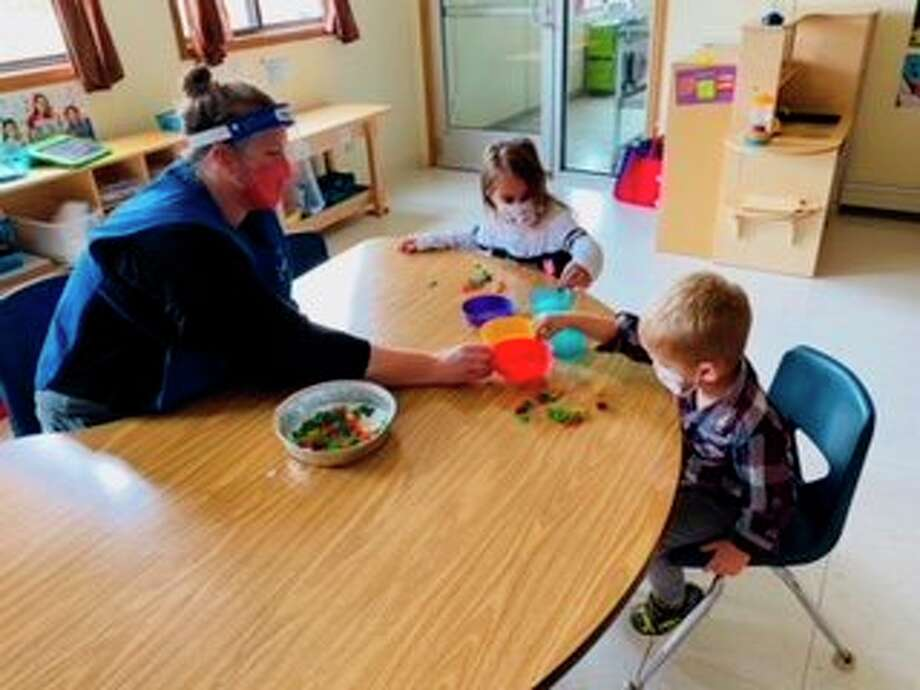 Head Start students enjoy a color sorting activity while adhering to safety precautions at the Northern Manistee Child Development Center. (Courtesy photo)