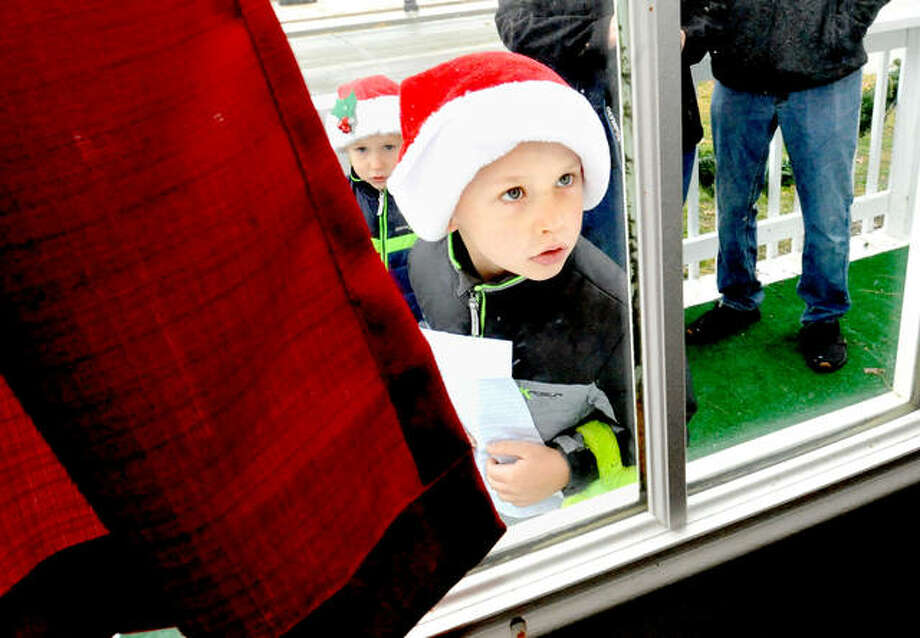 Grant Wiedman, 5, of Edwardsville peaks through the window at Santa as he and his little brother Theo, 3, behind Grant, wait their turn to see Santa during Santa at the Park in 2019. Photo: Thomas Turney | For The Intelligencer