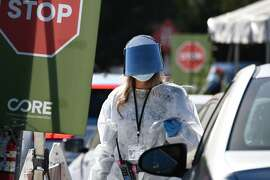 A healthcare worker wears protective gear at a coronavirus  testing site in Los Angeles, California on November 30, 2020 following the Thanksgiving holiday. - Los Angeles County's new stay-at-home restrictions took effect on November 30, 2020, one day after the county reported more than 5,000 new Covid-19 cases. (Photo by Robyn Beck / AFP) (Photo by ROBYN BECK/AFP via Getty Images)