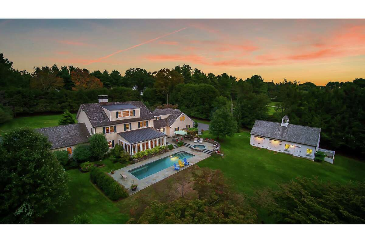 The property includes a modern barn with two vehicle bays and winterized workshop, large bluestone patio, a heated Gunite in-ground swimming pool, spa, and pergola.