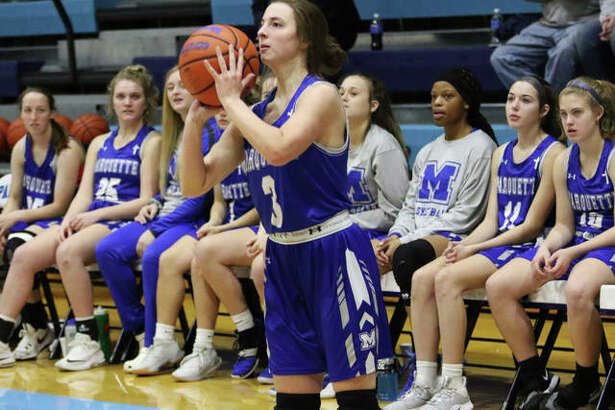 Marquette Catholic's Kamryn Fandrey sets to launch a 3-pointer while teammates look on from the bench during a game at the Jersey Holiday Tourney last season at Havens Gym in Jerseyville.