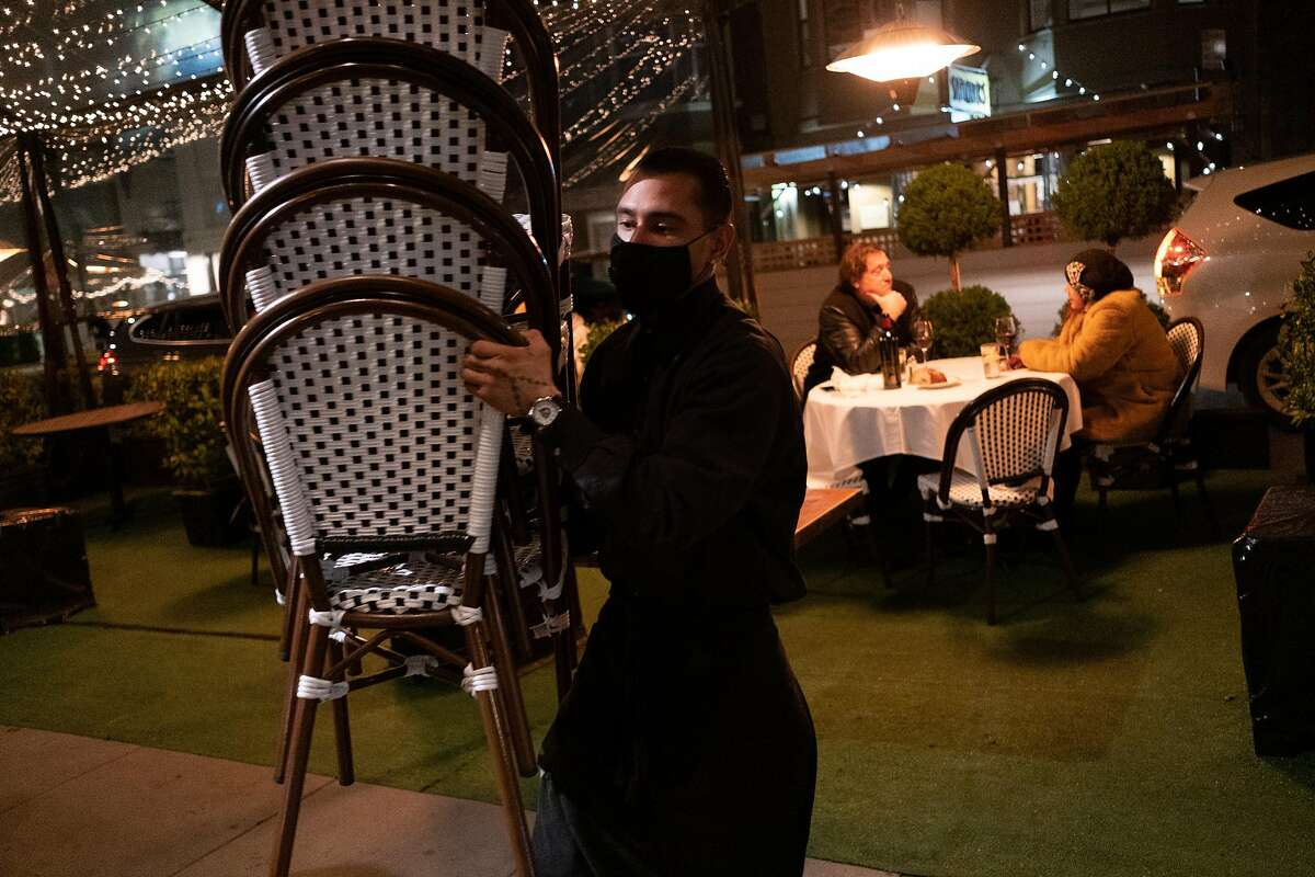 Andrew Recinos brings chairs indoors at Izzy's Steakhouse just before the mandatory 10 p.m. curfew takes effect in S.F.