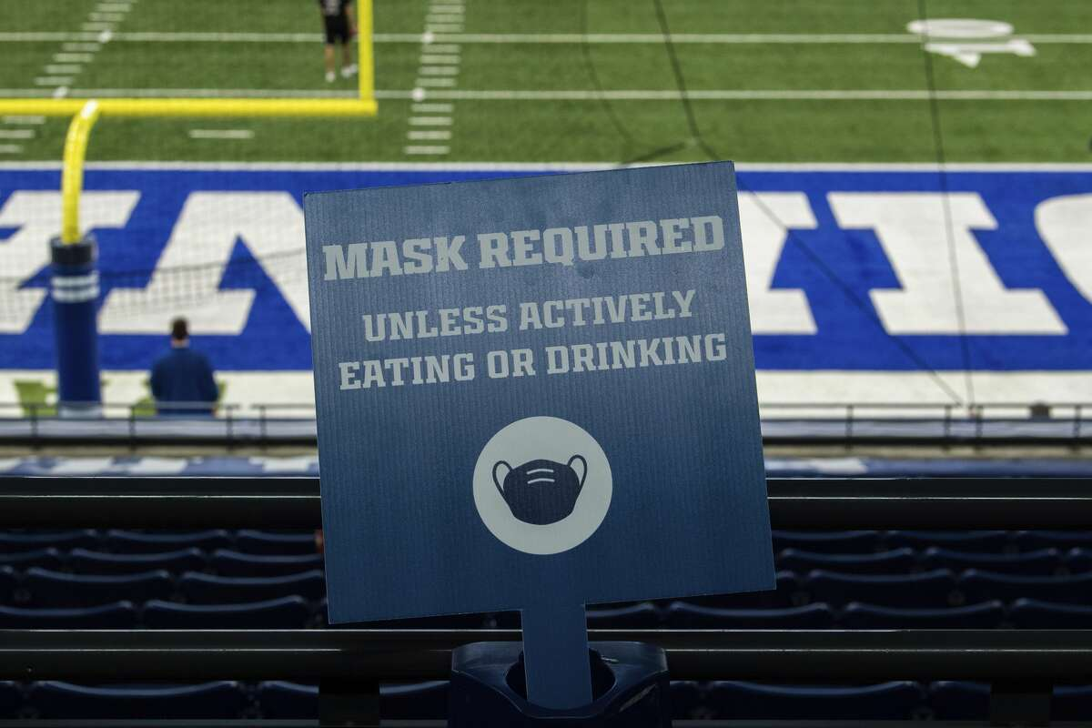 A sign requiring mask for fans sits in a cup holder during an NFL football game on Sunday, Nov. 29, 2020, in Indianapolis. (AP Photo/Zach Bolinger)