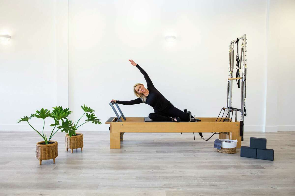 Pilates Instructor Liz Rivieccio demonstrates a pose on the Pilates apparatus called the reformer at the new Core Burn Pilates Yoga studio on Park Street in New Canaan. 2020