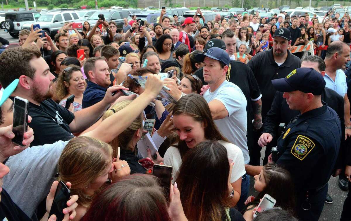 Fans throng Hollywood star Mark Wahlberg in June 2019 outside Wahlburgers at the Westfield Trumbull in Trumbull, Conn. The Trumbull restaurant is closed at the outset of the 2020 holiday season, with a sign stating