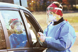 Melissa Bogle, a nurse practitioner, collects a swab Tuesday from a person using the Madison County Health Department's drive-through COVID-19 testing site on the north side of Gordon Moore Park in Alton. Due to a high volume of positive testing, the Alton School District announced Tuesday it will stick with remote-only instruction through Dec. 22.
