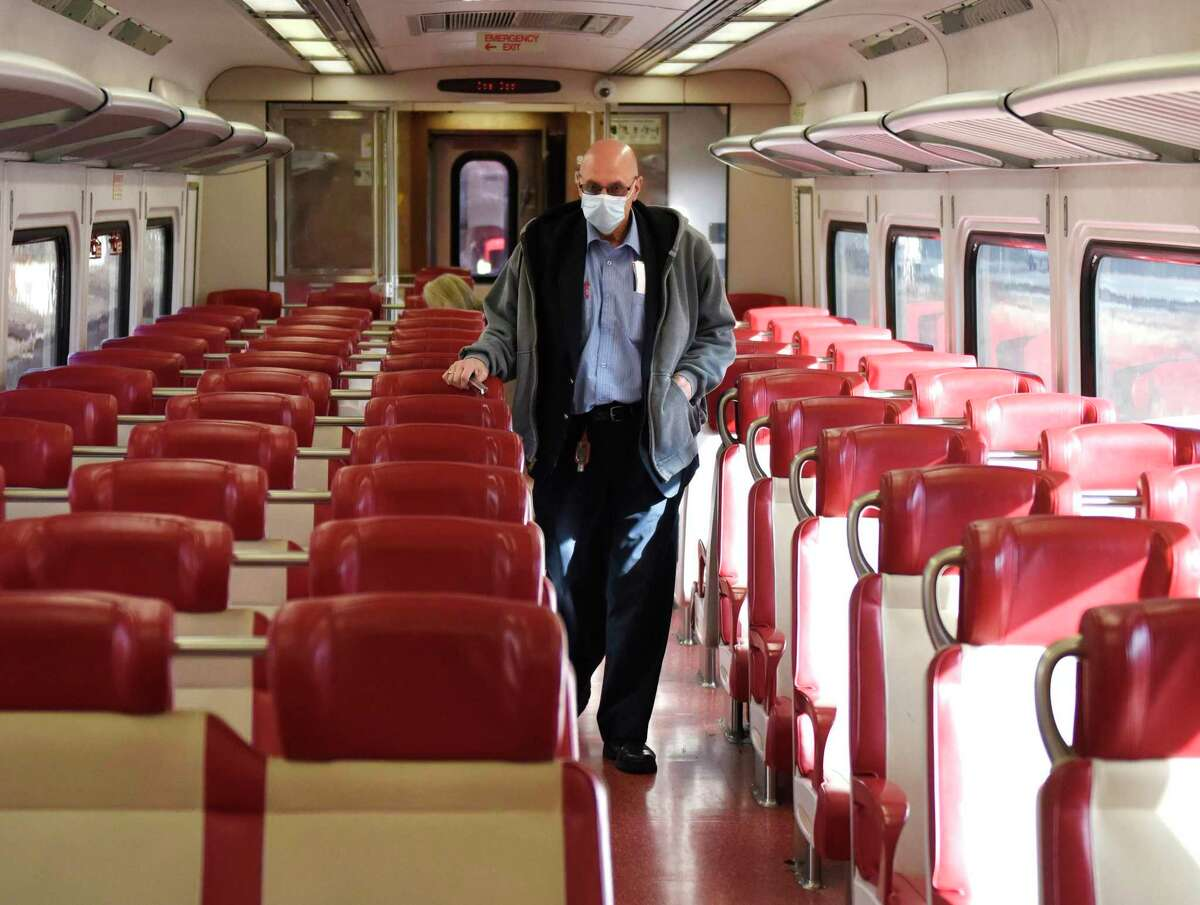 A Metro-North conductor collects tickets on the local train between Greenwich and Stamford, Conn. on Tuesday, Dec. 1, 2020. New Haven Line ridership is down 80 percent and service has been reduced 38 percent as the railroad awaits crucial federal aid.