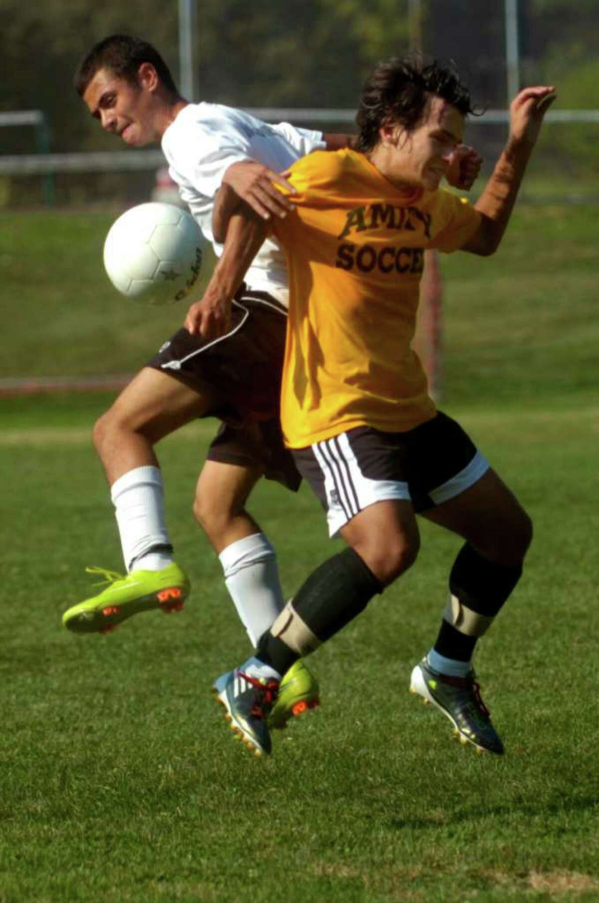 Trumbull's Anthony Teixera, left, and Amity's Ricky Mayer, right, both jump for the ball during a soccer scrimmage against on Thursday, September 2, 2010.