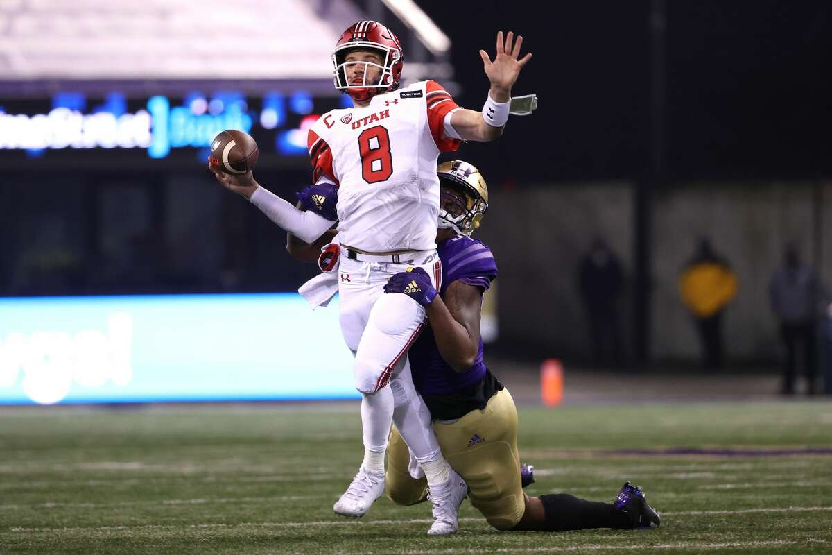 SEATTLE, WASHINGTON - NOVEMBER 28: Jake Bentley #8 of the Utah Utes fumbles the ball while being tackled by Zion Tupuola-Fetui #58 of the Washington Huskies in the first quarter at Husky Stadium on November 28, 2020 in Seattle, Washington. (Photo by Abbie Parr/Getty Images)