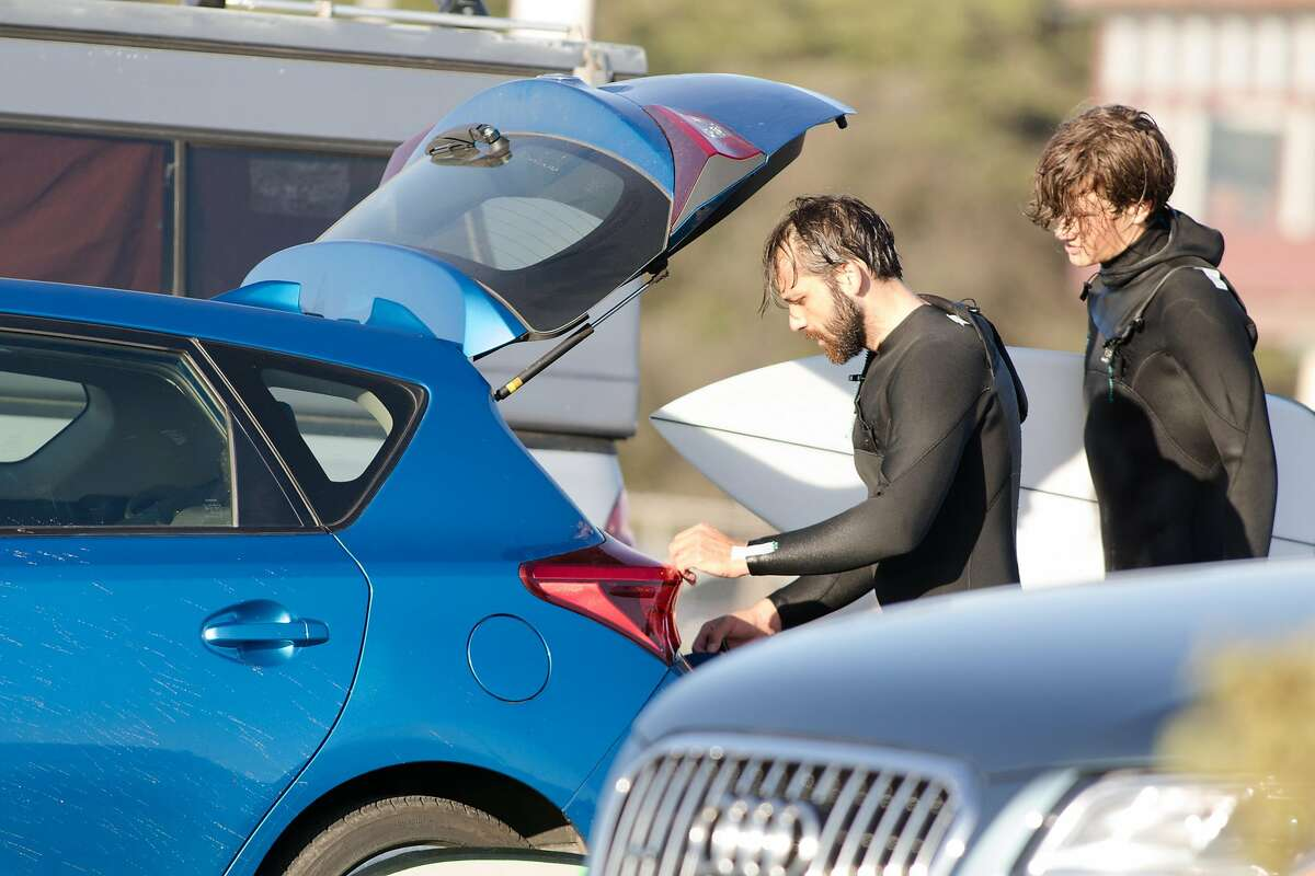Surfers put away items in their car after surfing at Ocean Beach in San Francisco on Nov. 27, 2020. There have been reports of increased car break-ins and car thefts at Ocean Beach and other surfing beaches in the Bay Area.