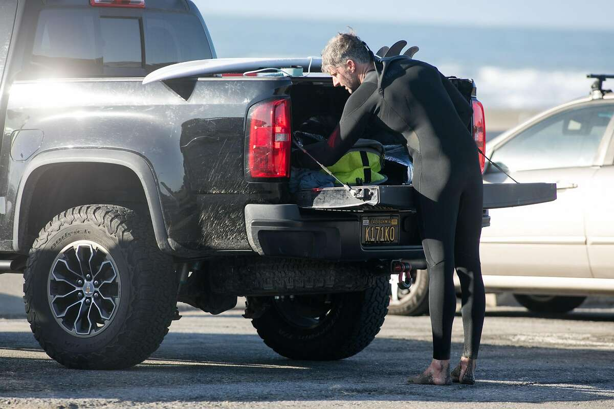 A surfers removes items from the trunk of his vehicle in the parking lot at Ocean Beach in San Francisco on Nov. 27, 2020. There have been reports of increased car break-ins and car thefts at Ocean Beach and other surfing beaches in the Bay Area.