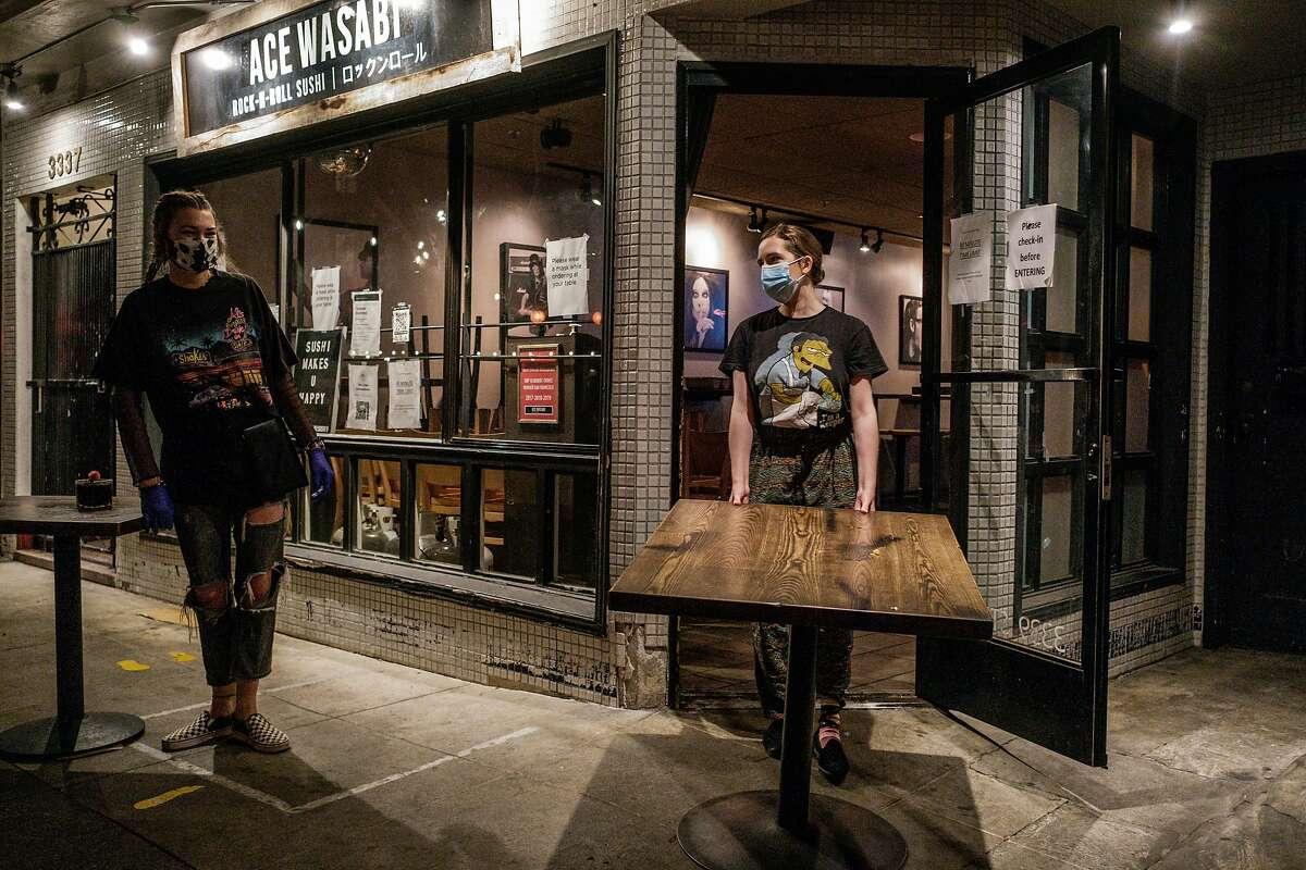Megan McCann (left) and Miranda Lehr bring tables indoors at Ace Wasabi ahead of S.F.'s 10 p.m. curfew.