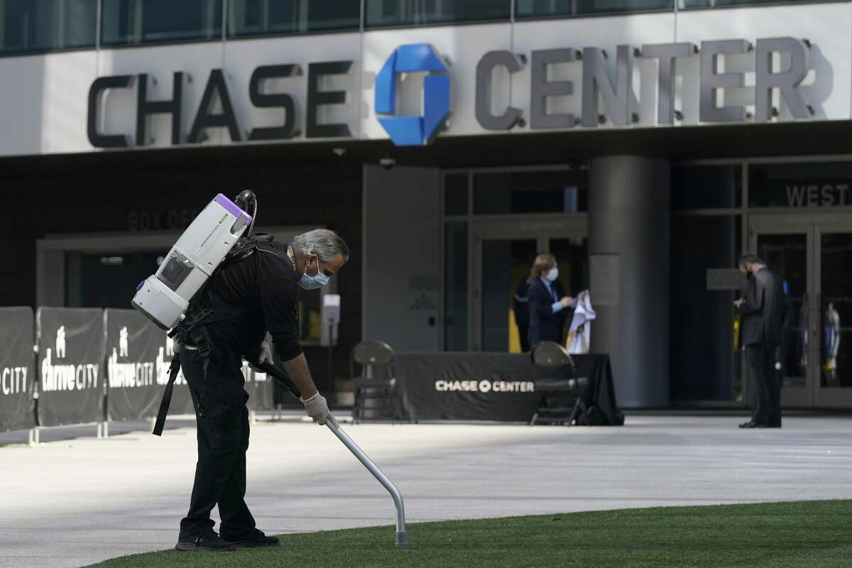 A man cleans outside of the Chase Center, the home of basketball's Golden State Warriors, in San Francisco, Thursday, Nov. 19, 2020. (AP Photo/Jeff Chiu)