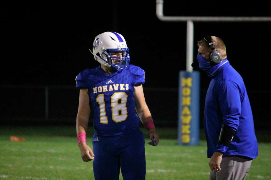 Morley Stanwood quarterback Aaron Moore talks with assistant coach James Nelson during the Lakeview game. (Pioneer file photo)