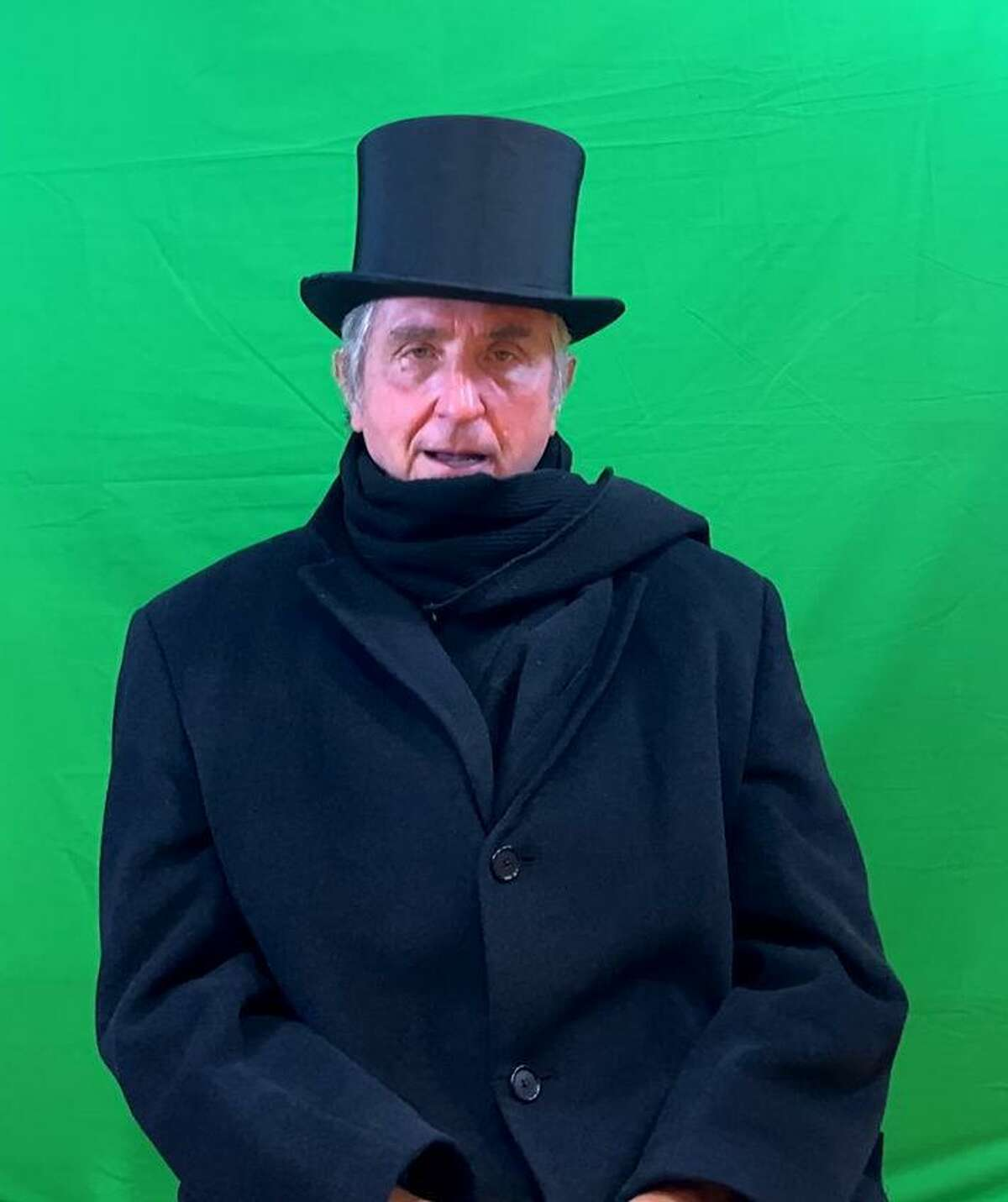 Peter Eldridge of the New Canaan Men's Club, dressed as Scrooge, in front of the green screen used while making the production.