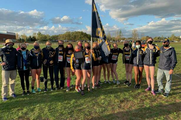 Manistee cross country coach Eric Thuemmel (left) poses with the Manistee girls team after they won the girls program's first-ever conference title. (News Advocate file photo)