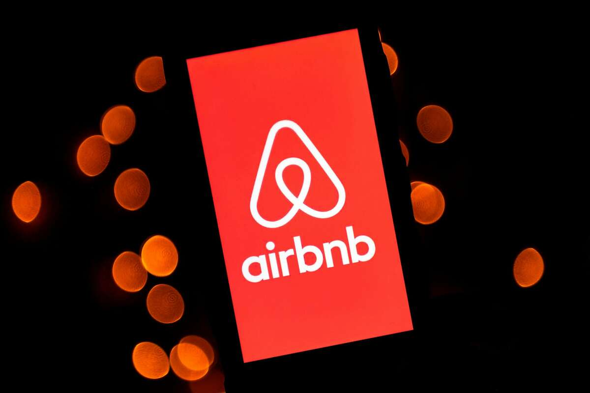 FILE-- In this file illustration photo taken on November 22, 2019 shows the logo of the online lodging service Airbnb displayed on a tablet in Paris. Airbnb says it will be blocking and canceling all reservations in the Washington, D.C. area during the week of the presidential inauguration.