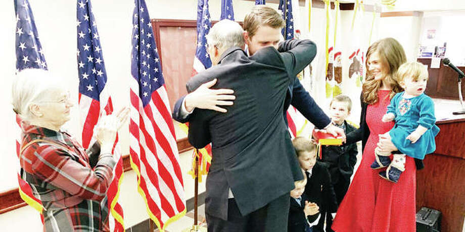 Former Madison County State's Attorney and Illinois State Senator Bill Haine and his son, new Madison County State's Attorney Thomas Haine, hug after Bill Haine swore in his son during a ceremony Tuesday at the Madison County Administration Building. Because of COVID, the swearing in of several officials was spread out to every half hour.