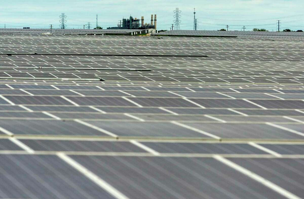 Fields of solar panels at OCI Solar Power's Alamo 1 Solar Farm are seen Sept. 23, 2020 as CPS Energy's coal-powered electric plant is seen in the background.