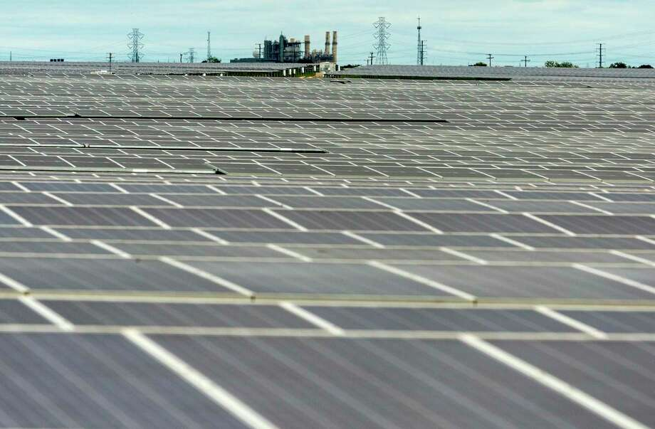 Fields of solar panels at OCI Solar Power's Alamo 1 Solar Farm are seen Sept. 23, 2020 as CPS Energy's coal-powered electric plant is seen in the background. Photo: William Luther, Staff / Staff / ©2020 San Antonio Express-News