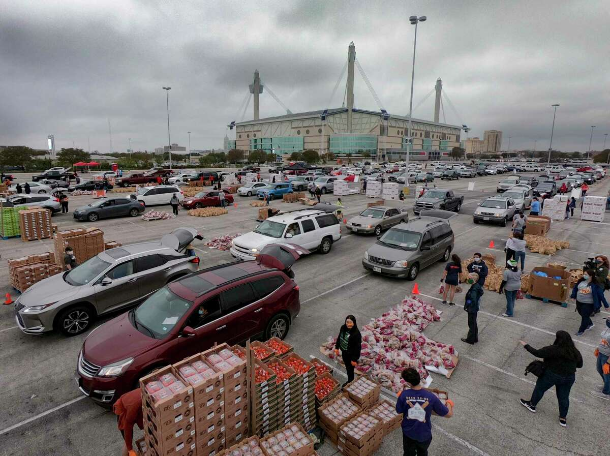 San Antonio Food Bank volunteers load food into waiting vehicles at the Alamodome on Nov. 24. More than 2,000 families were served at the event. Hunger continues to be a problem for many area families as the pandemic tightens its grip on some sectors of the economy.
