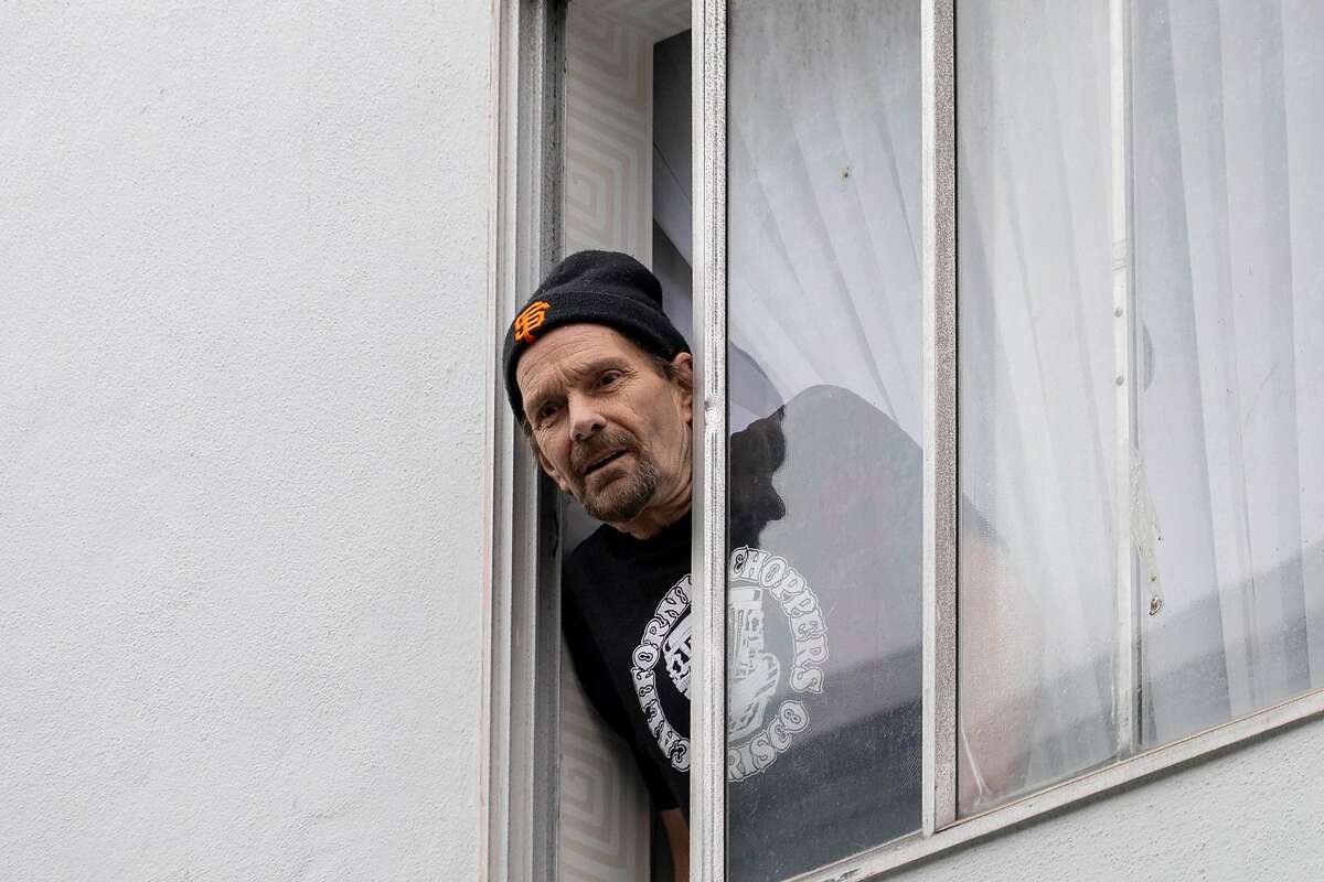 Mark Masonete looks out the window of his hotel room in April. S.F. pays to house homeless people.