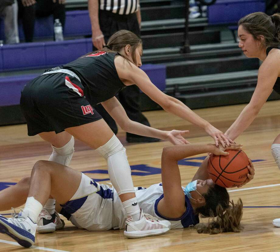 Midland High's Noemi Areiga battles for a loose ball with Lubbock Cooper's Autumn Moore and Catalina Cortez 12/01/2020 at the Midland High gym. Tim Fischer/Reporter-Telegram Photo: Tim Fischer, Midland Reporter-Telegram