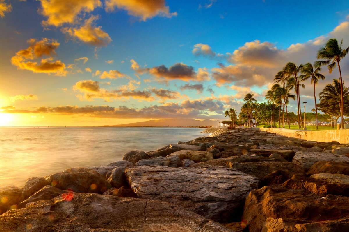 This could be your office: An ocean sunset over rocks and palm trees at beachfront park Kaka'ako on O'ahu, Hawaii.