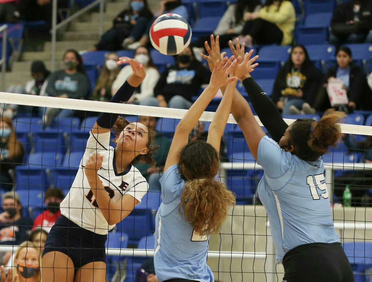 Brandeis' Jalyn Gibson (12) scores against Harlan's Dahlia De Los Santos (02) and Mackenzie Vernon (15) in the Region IV-6A semifinal volleyball playoff game at Northside Sports Gym on Tuesday, Dec. 1, 2020. The Broncos defeated the Hawks in three consecutive games to take the match and move on in the playoffs.