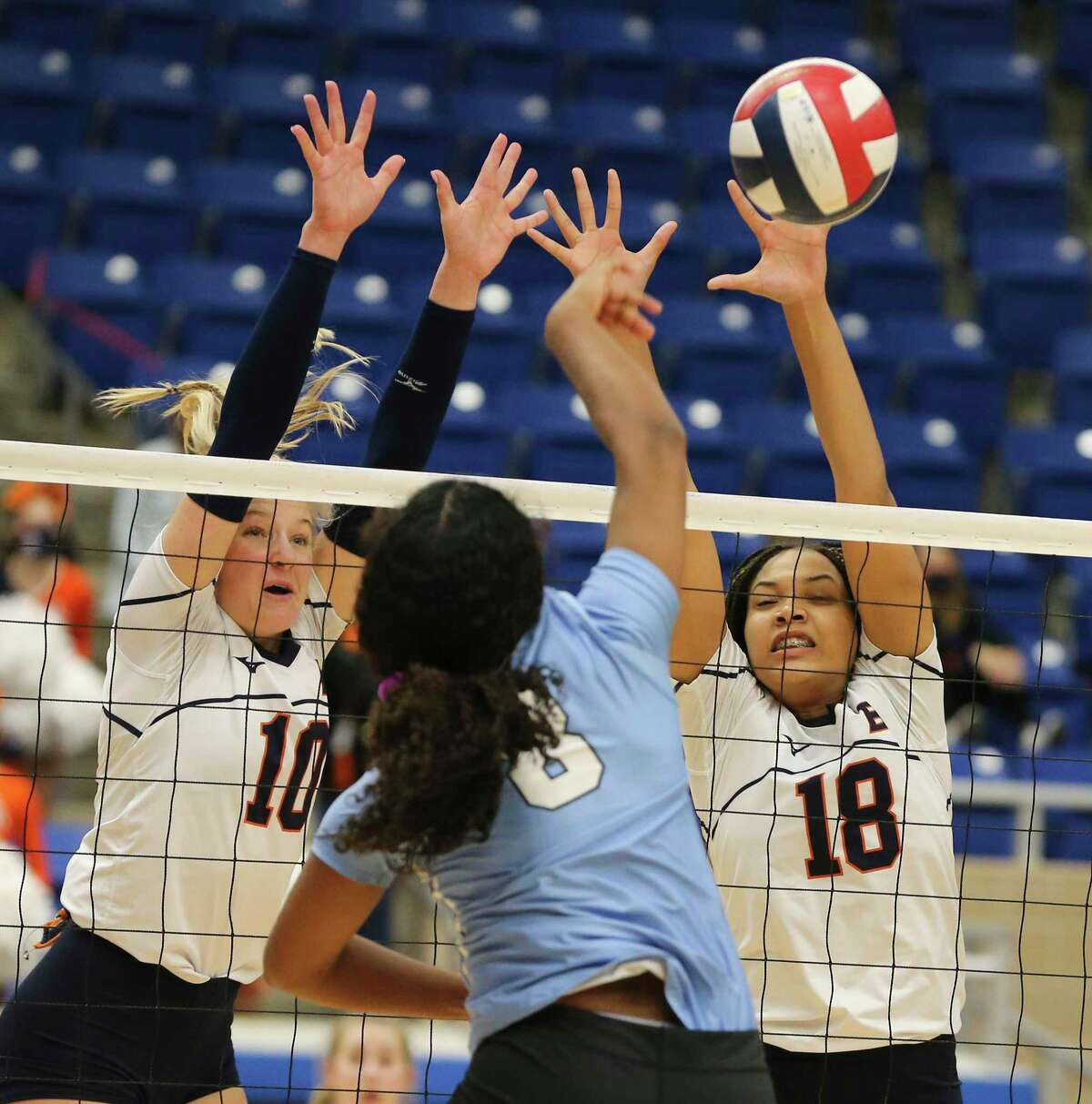 Brandeis' Carlee Pharris (10) and Austin Smoak (18) go up to block a shot by Arissa Willis (08) during their Region IV-6A semifinal volleyball playoff game at Northside Sports Gym on Tuesday, Dec. 1, 2020. The Broncos defeated the Hawks in three consecutive games to take the match and move on in the playoffs.