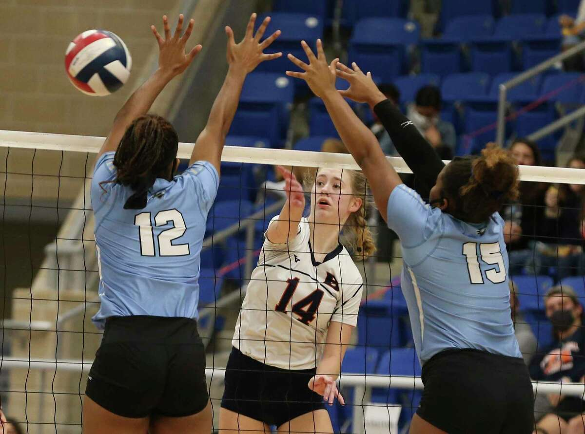 Brandeis' Emma Halstead (14) hits through Harlan's Trinity Iverson (12) and Mackenzie Vernon (15) in the Region IV-6A semifinal volleyball playoff game at Northside Sports Gym on Tuesday, Dec. 1, 2020. The Broncos defeated the Hawks in three consecutive games to take the match and move on in the playoffs.