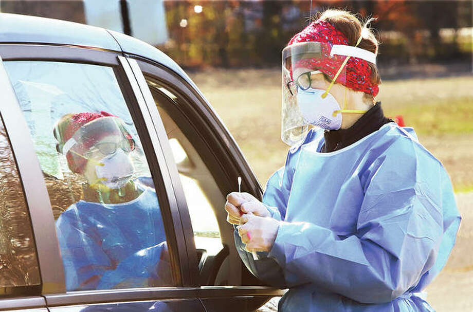 Melissa Bogle, a nurse practitioner, collects a swab Tuesday from a person using the Madison County Health Department's drive-through COVID-19 testing site on the north side of Gordon Moore Park in Alton.