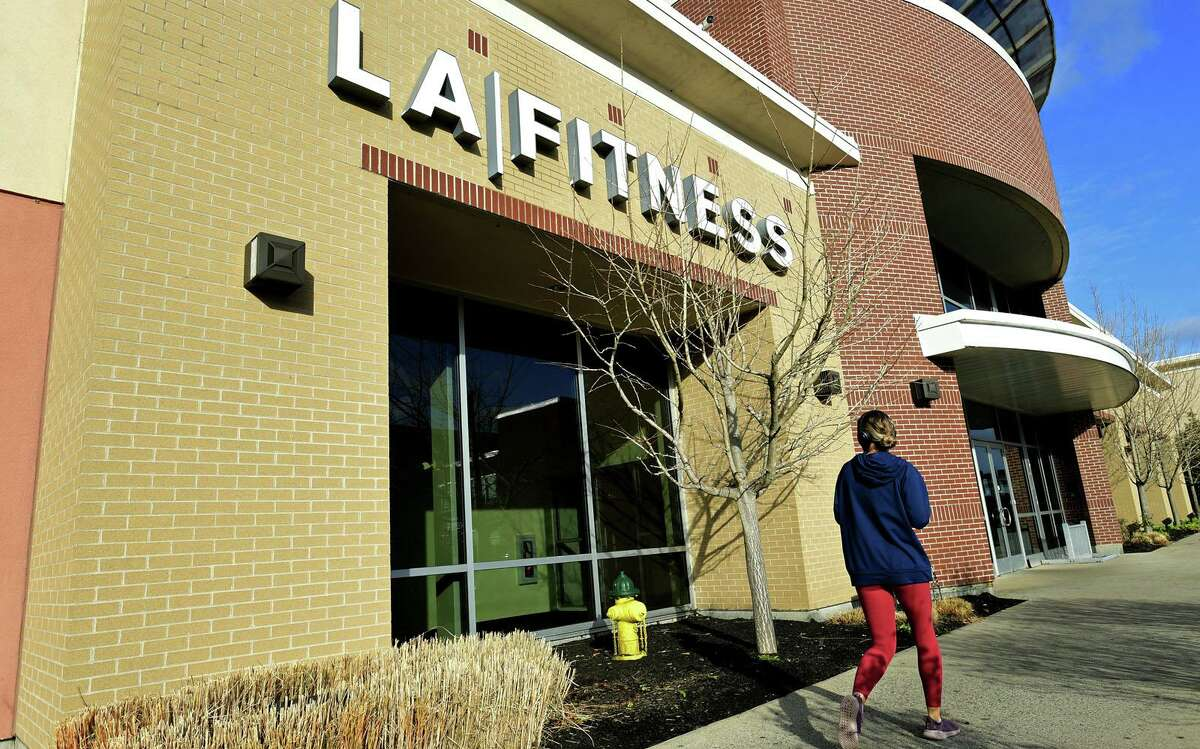 Patrons visit the LA Fitness Norwalk location to find that it has been closed Wednesday, December 2, 2020, at iPark in Norwalk, Conn. The Norwalk Health Department and Norwalk Police Department signed a closure order for LA Fitness today due to several repeated violations of State of Connecticut sector rules. Violations include patrons not wearing facemasks or other cloth face coverings, failure to maintain six feet of space between equipment and people, and failure to enforce the revised capacity limits.